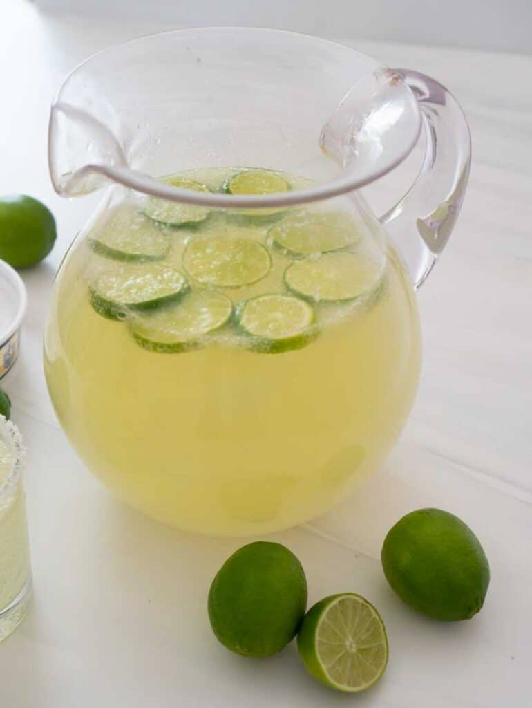 nonalcoholic margarita punch in clear pitcher with limes