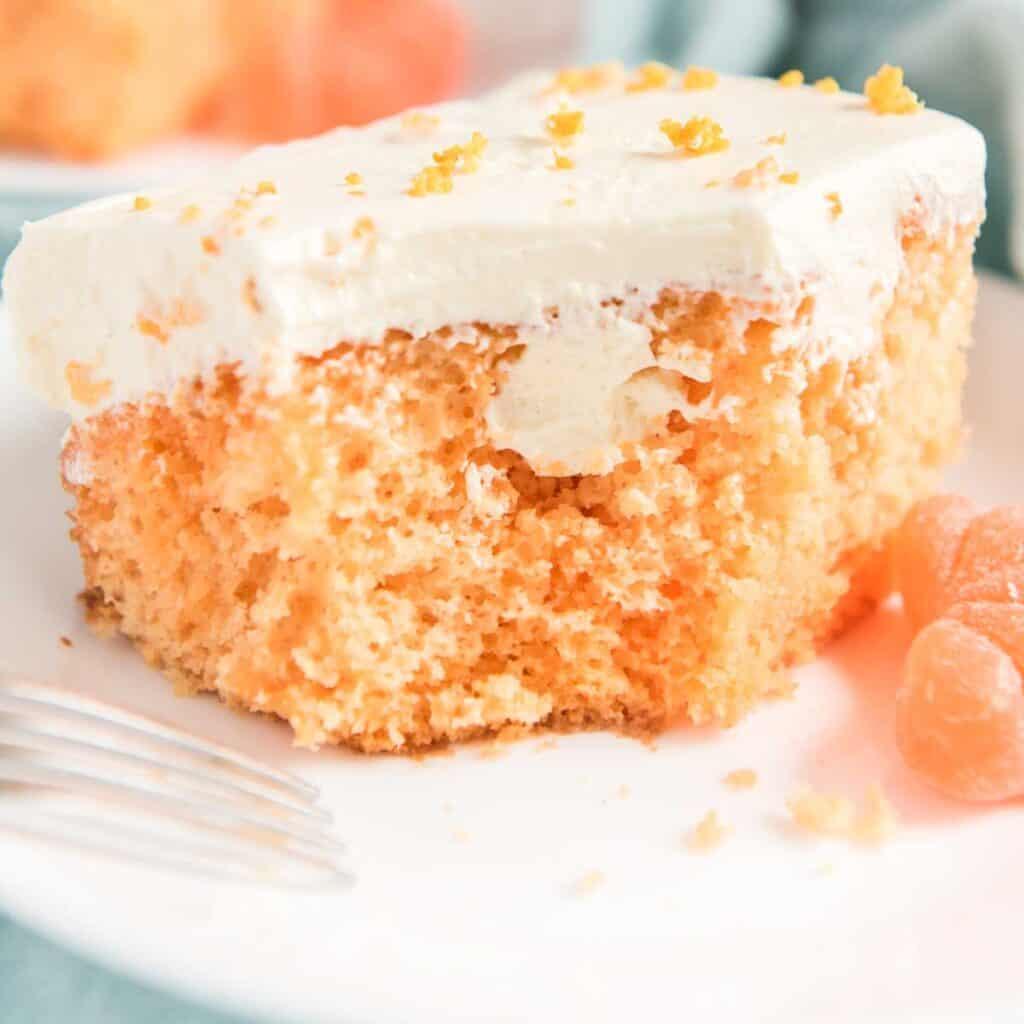 orange creamsicle poke cake on white plate