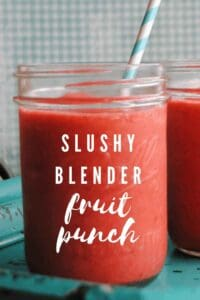 red slushy punch in a mason jar with straw and text reading slushy blender fruit punch