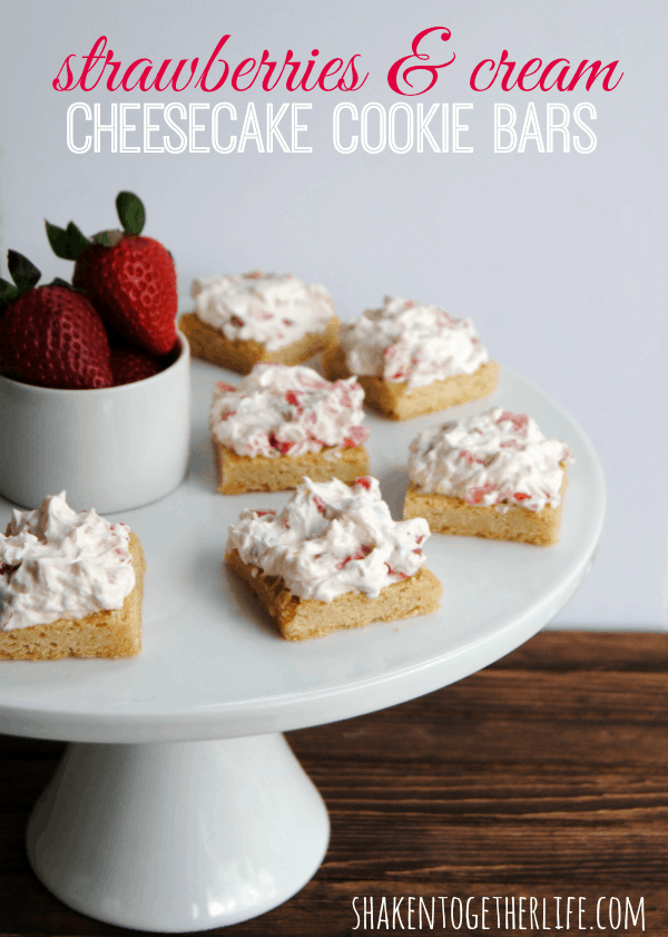 Soft sugar cookie bars heaped with fluffy strawberry cheesecake frosting!