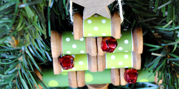 Paper wrapped wooden spools make a charming Christmas tree ornament - add jingle bell ornaments and a gold star, too!