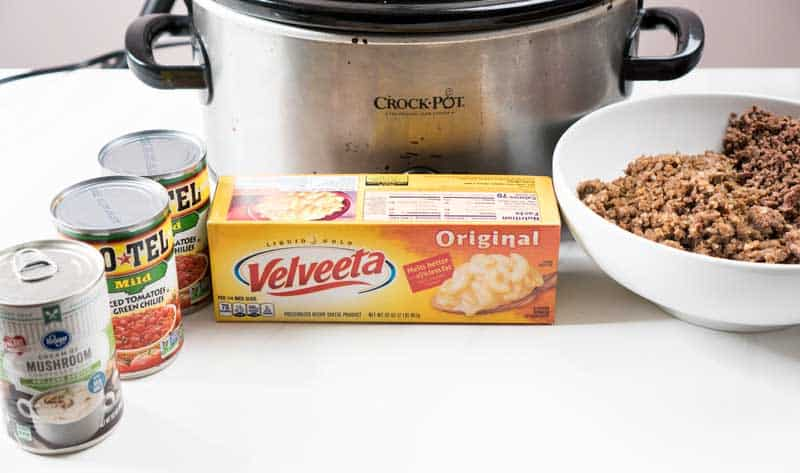 crock pot with velveeta, rotel, cream of mushroom soup, ground beef and ground sausage for slow cooker queso cheese dip