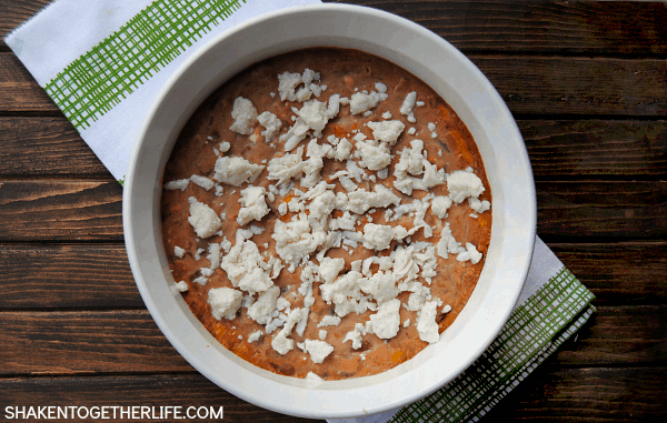 Creamy Bean Dip is an easy appetizer that is perfect for Cinco de Mayo! Beans, spices and cheese are baked until bubbly, then topped with crumbled cotija!