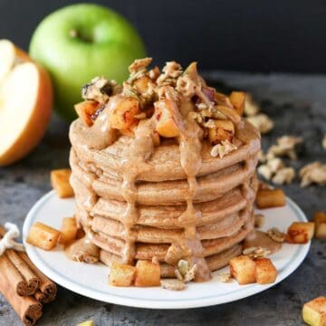 stack of pancakes with apples and syrup