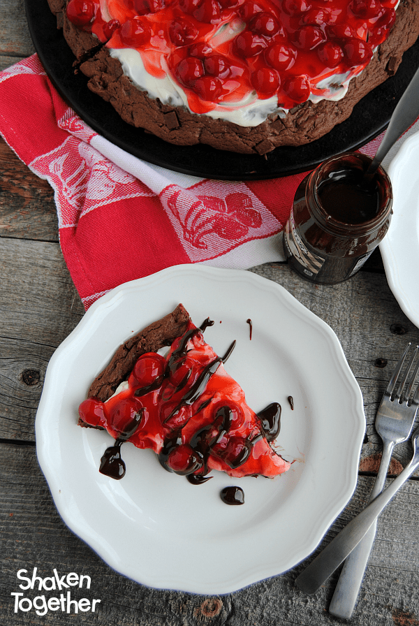 With a double chocolate cookie crust, a sweet cheesecake spread, tart cherries and a drizzle of warm hot fudge, this Cherry Cheesecake Chocolate Dessert Pizza is dessert perfection!