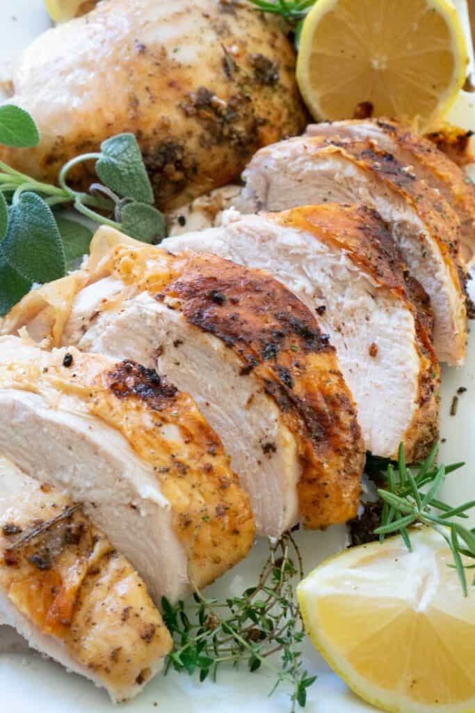 sliced roasted turkey breast on plate with herbs