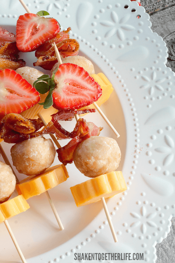 Berry Brunch Kabobs on white plate with strawberry bacon cheese doughnut holes