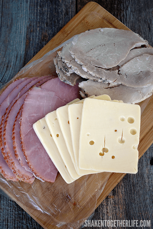 deli slice sweet ham, seasoned pork and swiss cheese in thick slabs on a cutting board