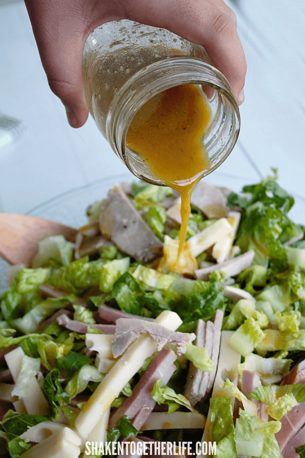 pouring a  tangy mustard vinaigrette on a hearty, low carb Cuban Cobb Salad!