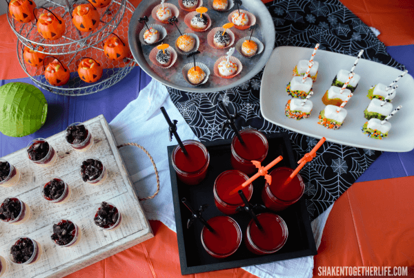 Our Halloween Dessert Bar got layers of color and textures with tablecloths, a gauzy white towel and spider web fabric.