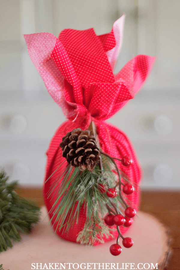 4 Easy Ways to Wrap Candles for Gifts: use a fabric fat quarter and a holiday foliage pick to dress up a medium jar candle!