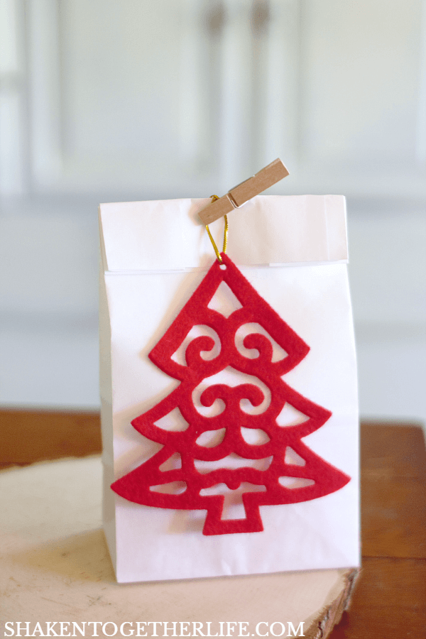 4 Easy Ways to Wrap Candles for Gifts: a simple paper lunch bag, mini clothespin and a felt ornament make giving a small tumbler candle simple and affordable!
