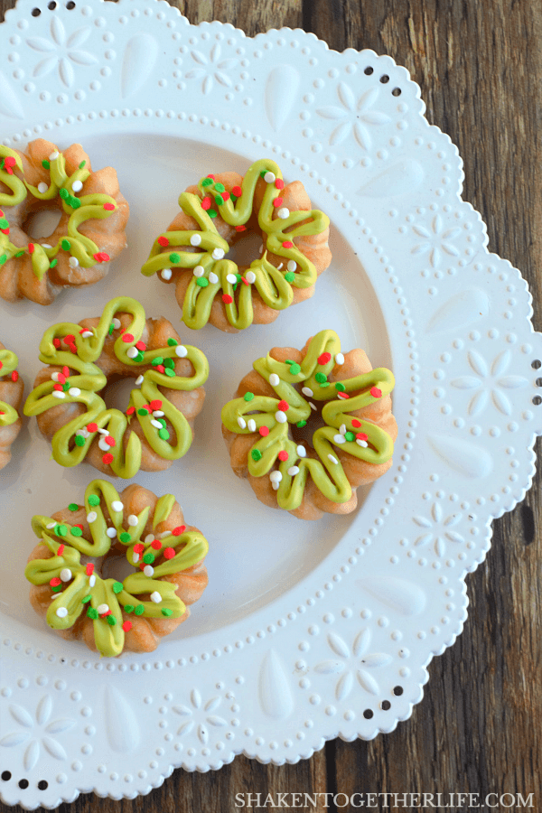 Mini Donut Wreaths are perfect for Christmas morning breakfast! Let the kiddos help with the piping and sprinkles!