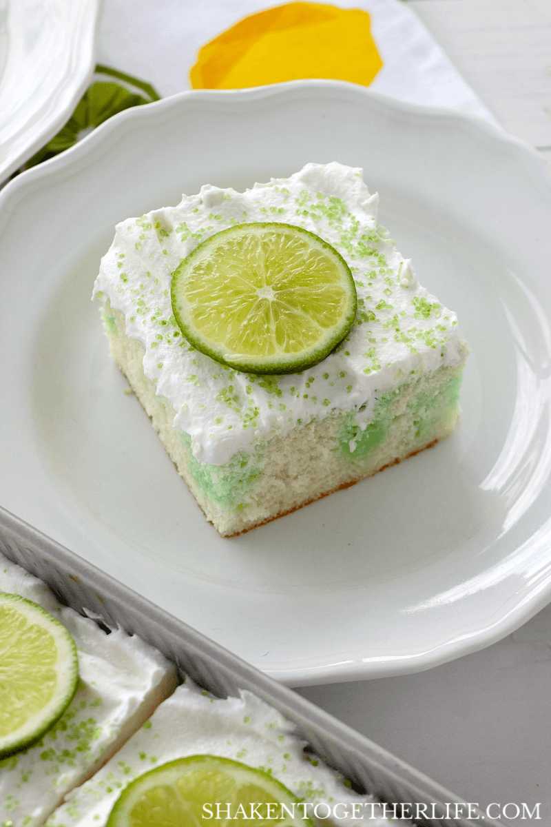 Lime Poke Cake is simple and stunning! The cake is moist and drenched in tangy lime Jell-o then topped with fluffy whipped topping and lime slices - YUM!