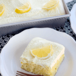 Triple Lemon Poke Cake on white plate