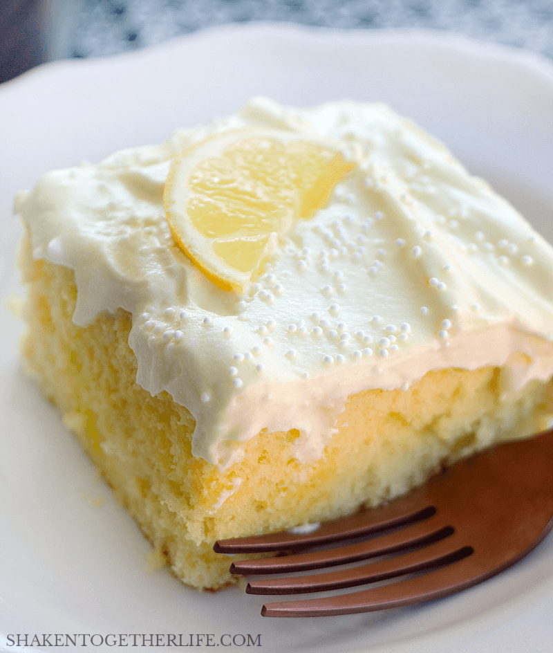 lemon poke cake topped with lemon slice on white plate