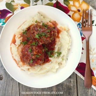 Classic Porcupine Meatballs are comfort food at its finest! Hearty beef and rice meatballs bake in a simple but savory tomato sauce!