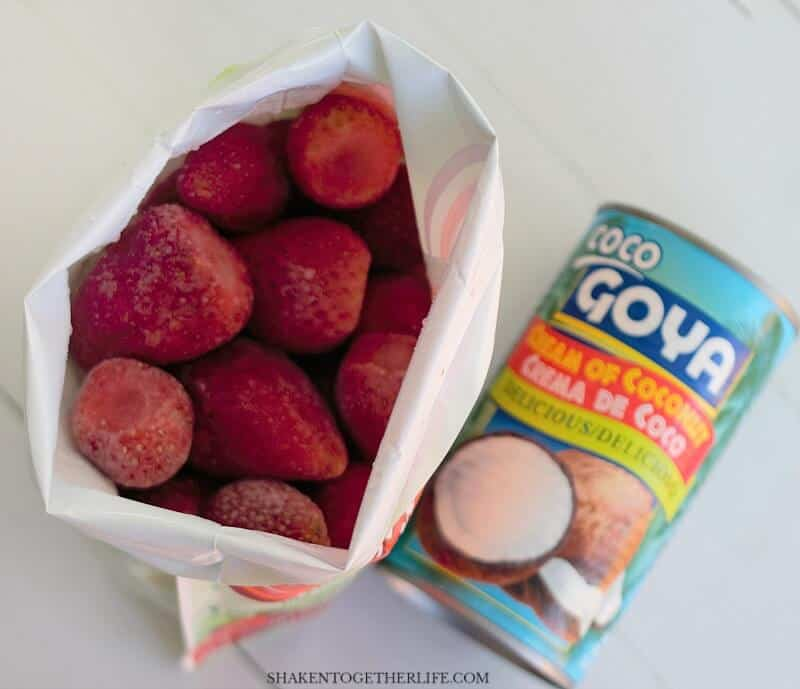overhead view of frozen strawberries and Goya cream of coconut