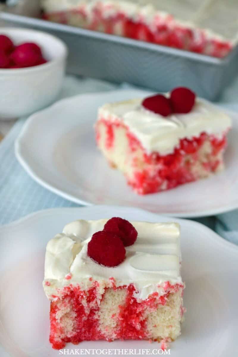 Raspberry Poke Cake is a soft white cake drenched in raspberry Jell-o, topped with whipped topping and then fresh raspberries. It is sweet and tangy, fruity and fabulous!