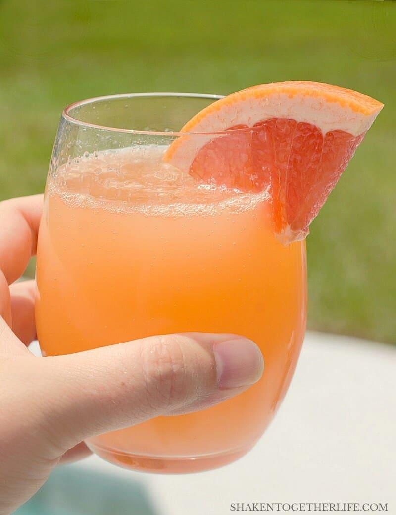 Ruby Red Grapefruit Mimosa with wedge of grapefruit garnish