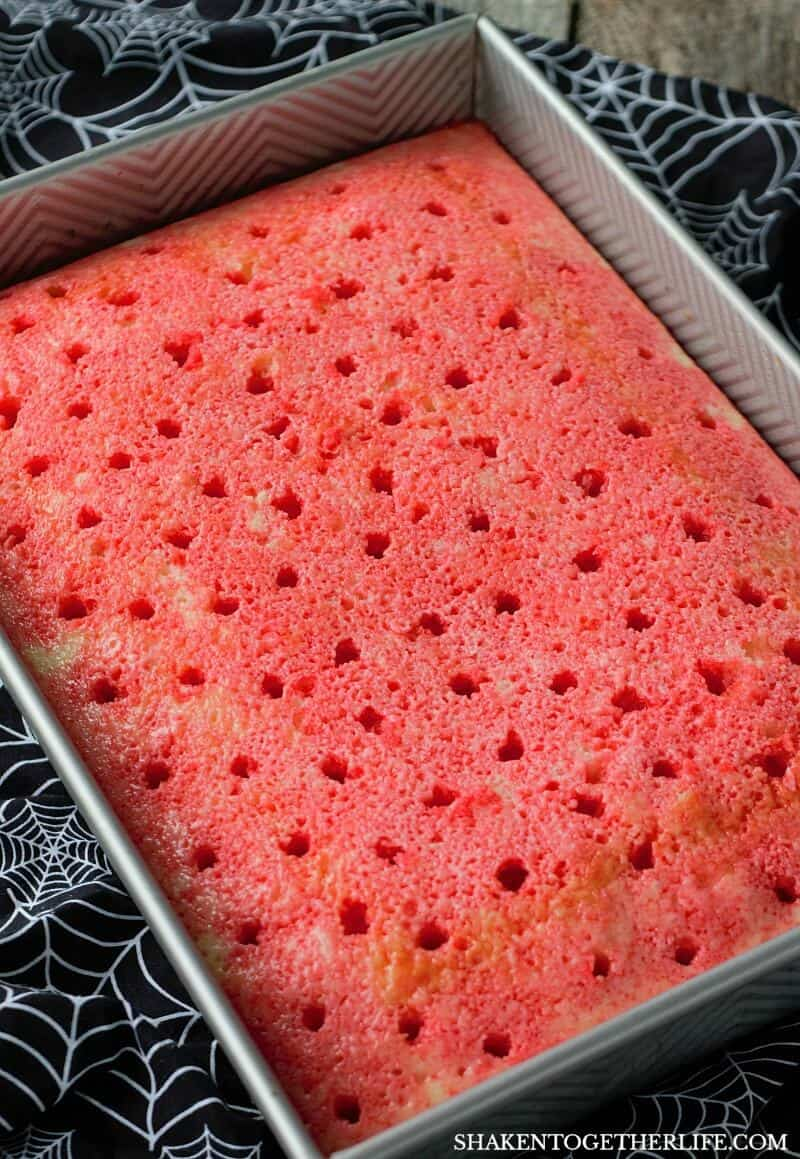 Cherry Vanilla Vampire Poke Cake starts with a vanilla cake soaked with cherry Jell-o