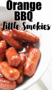 close up of little smokies cocktail sausages in orange barbecue sauce in white bowl
