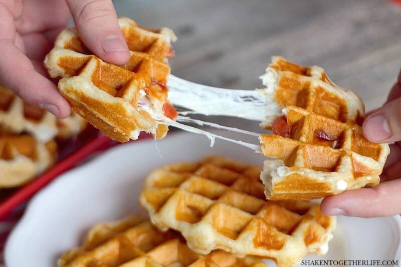 Pizza Stuffed Waffles - just look at that gooey melty cheese pull! This easy dinner recipe has just 4 ingredients and starts with refrigerator biscuits.
