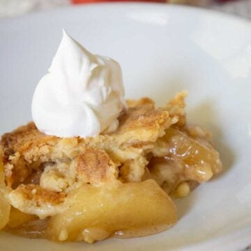 apple dump cake on white plate with whipped cream