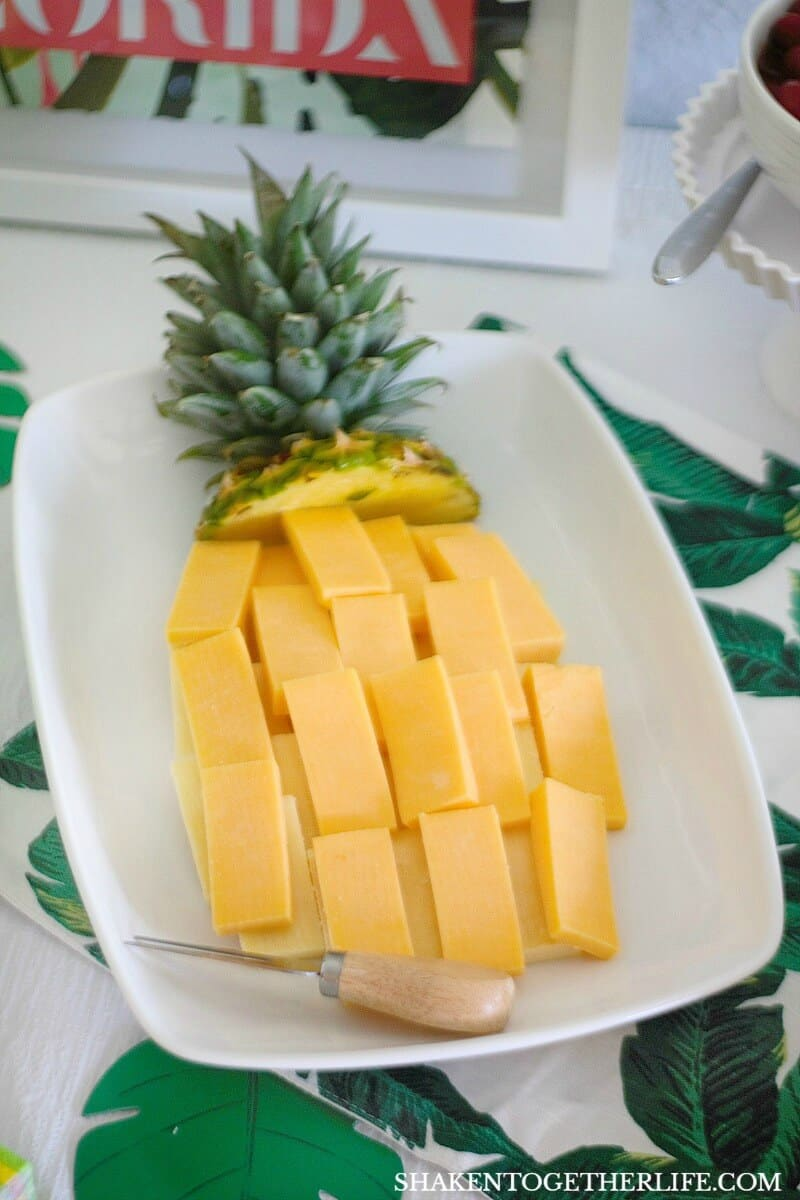 A pineapple shaped cheese tray is festive and easy to make for a Tropical Summer Craft Party! Ask the produce manager in your grocery store for the top of a pineapple to add to the cheese tray!