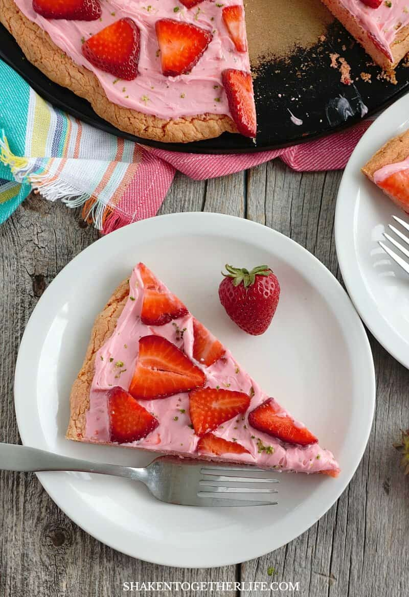 Strawberry Dessert Pizza from a Cake Mix is an easy breezy Summer dessert made with a strawberry cookie crust, strawberry frosting, fresh sliced strawberries and a sprinkle of lime zest!