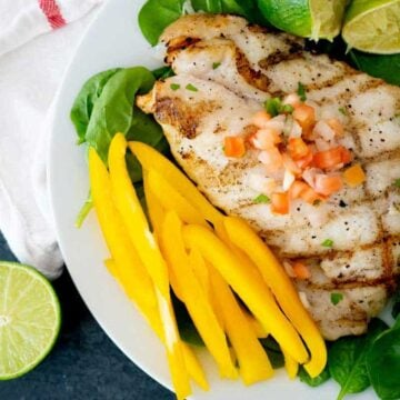 grilled grouper on plate with spinach and yellow bell pepper slices