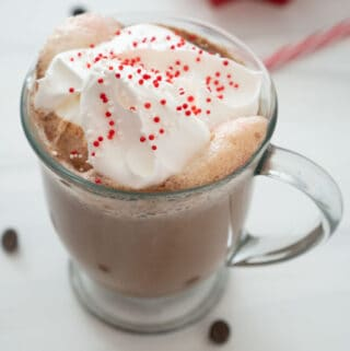 peppermint hot chocolate in glass mug with whipped cream and red and white sprinkles