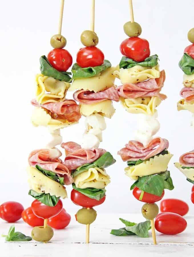 3 anitpasto skewers standing up on wood table