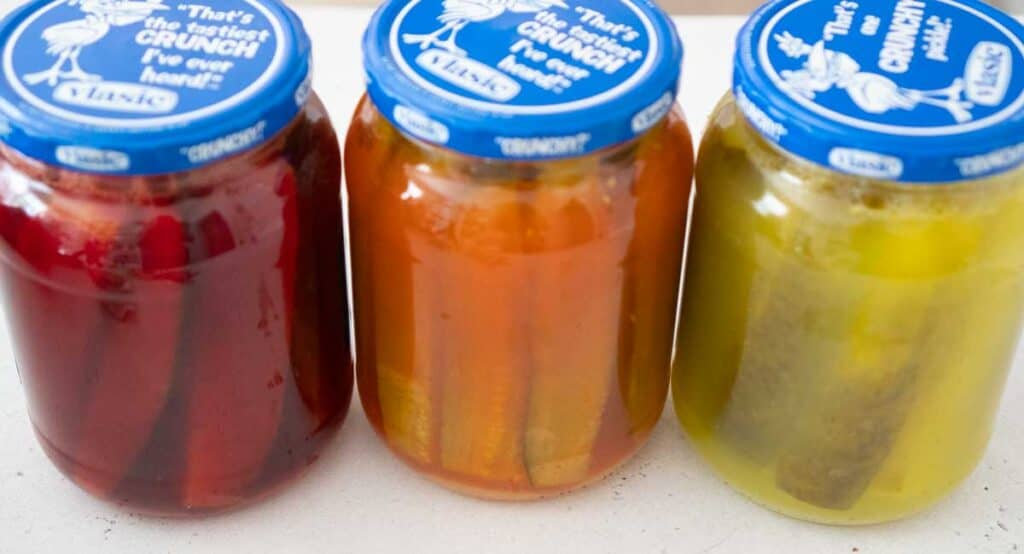 three jars of kool aid pickles, cherry, orange, and lemonade flavored