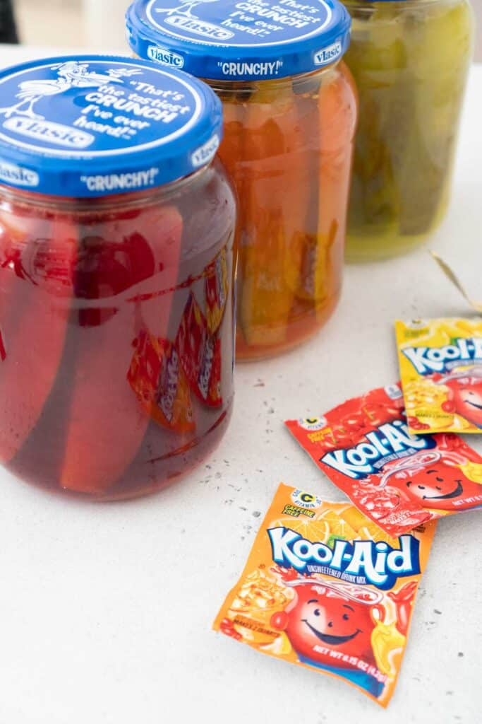 three jars of kool aid pickles and kool aid packets