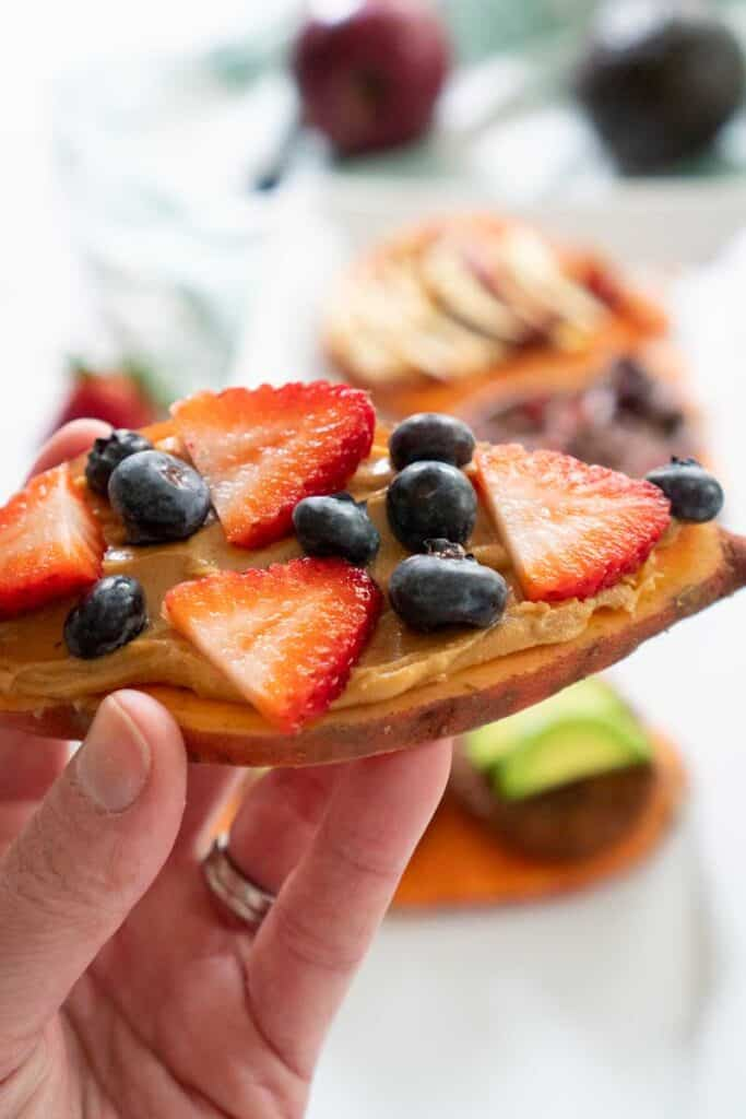 hand holding sweet potato toast with peanut butter and berries
