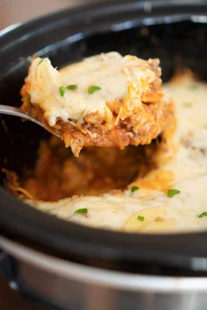 crock pot lasagna scooped out of slow cooker with large spoon