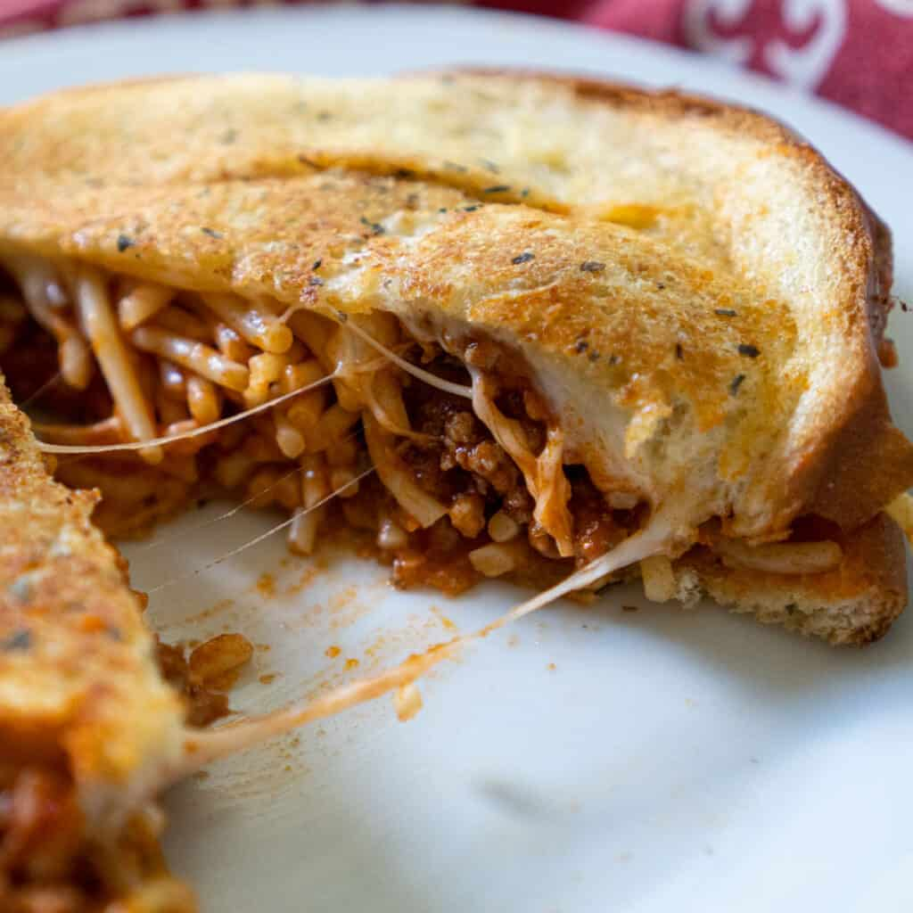spaghetti sandwich grilled cheese on white plate with red napkin