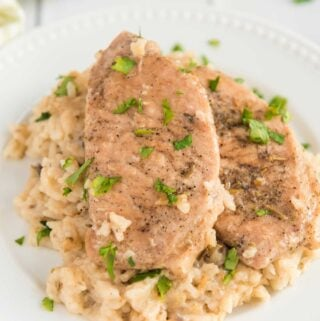 baked pork chops with mushroom rice on white plate with chopped parsley