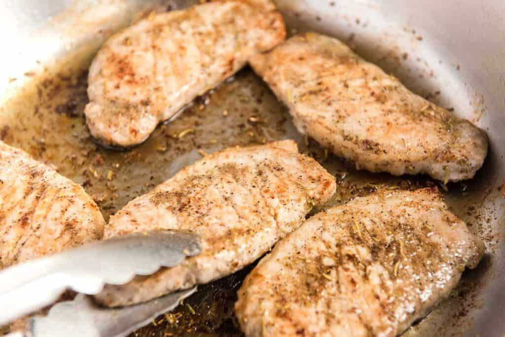searing pork chops in a skillet