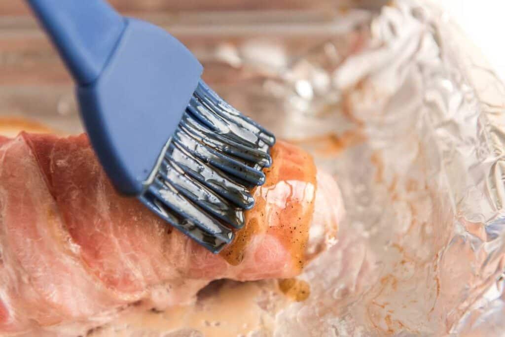 brushing glaze over bacon wrapped pork tenderloin