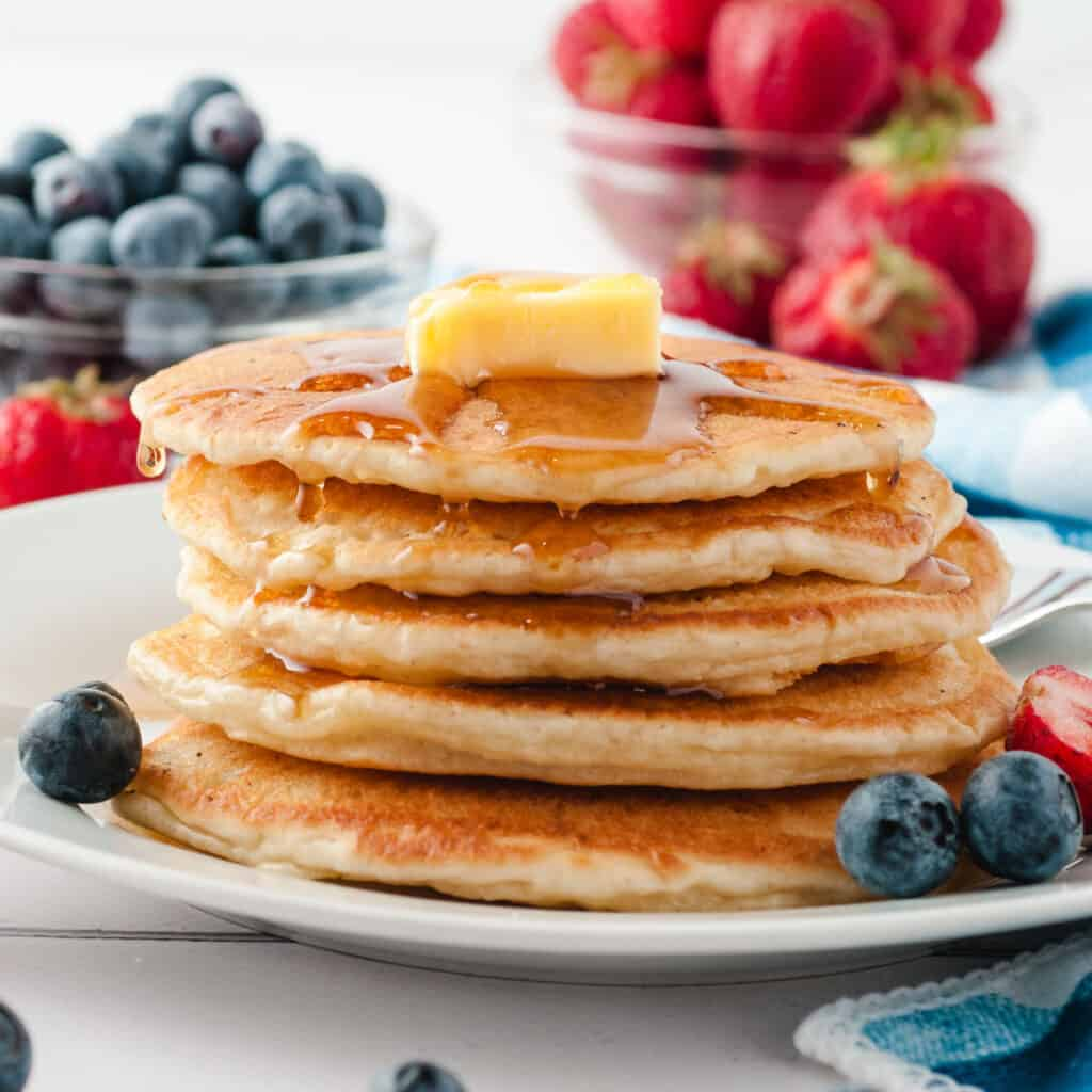 pancakes in stack on white plate with butter and syrup and strawberries and blueberries