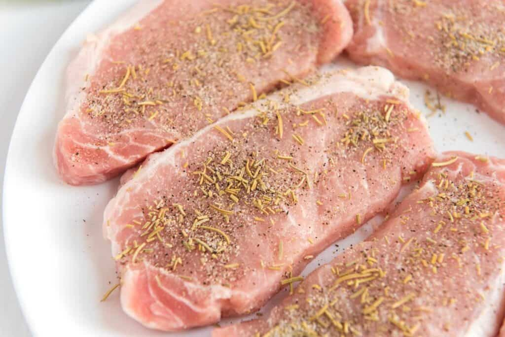 raw pork chops on white plate with herbs and seasonings