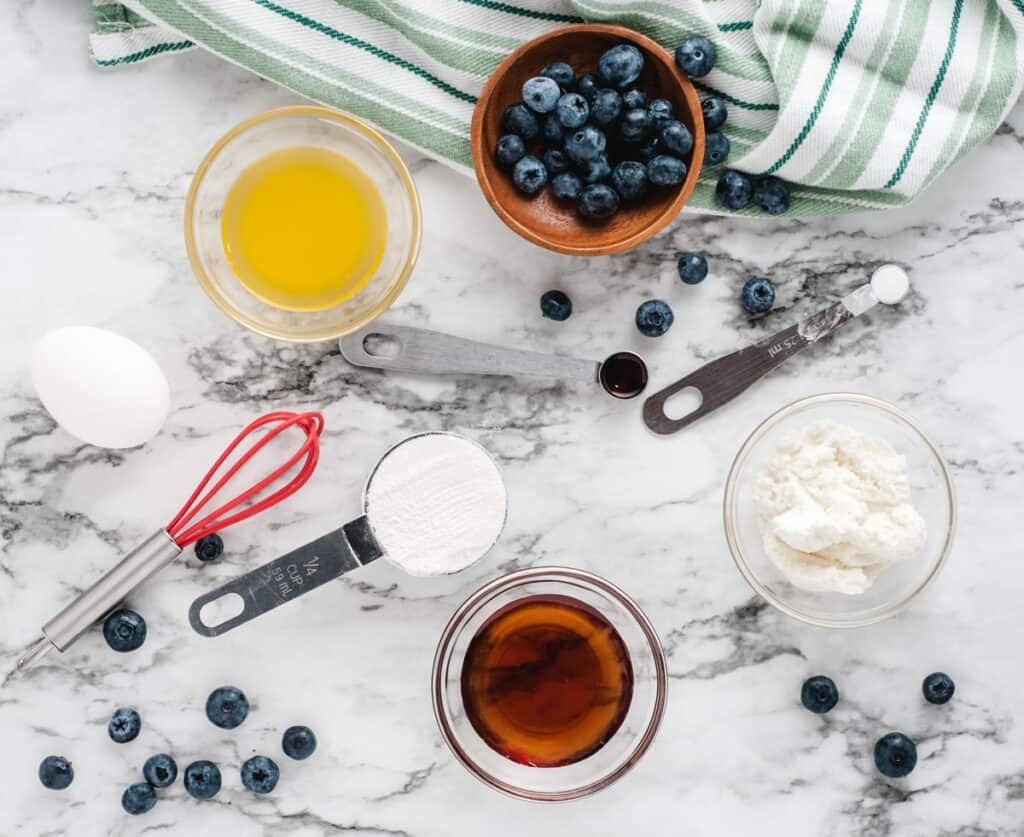 ingredients for blueberry mug cake on marble countertop