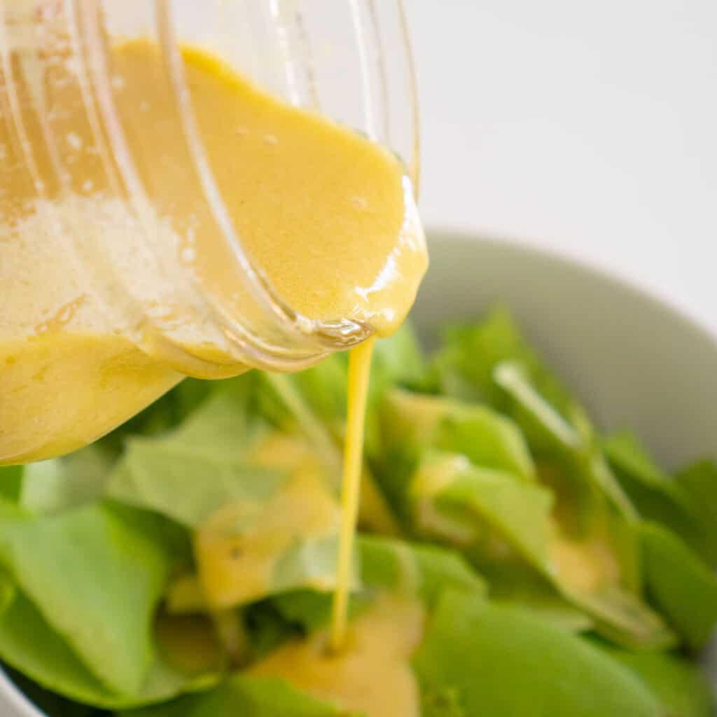 pouring homemade dijon vinaigrette over salad