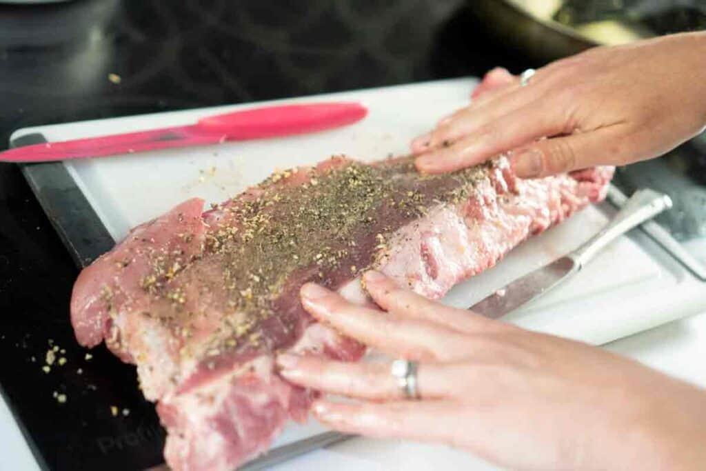 hand rubbing dry rub on rack of ribs