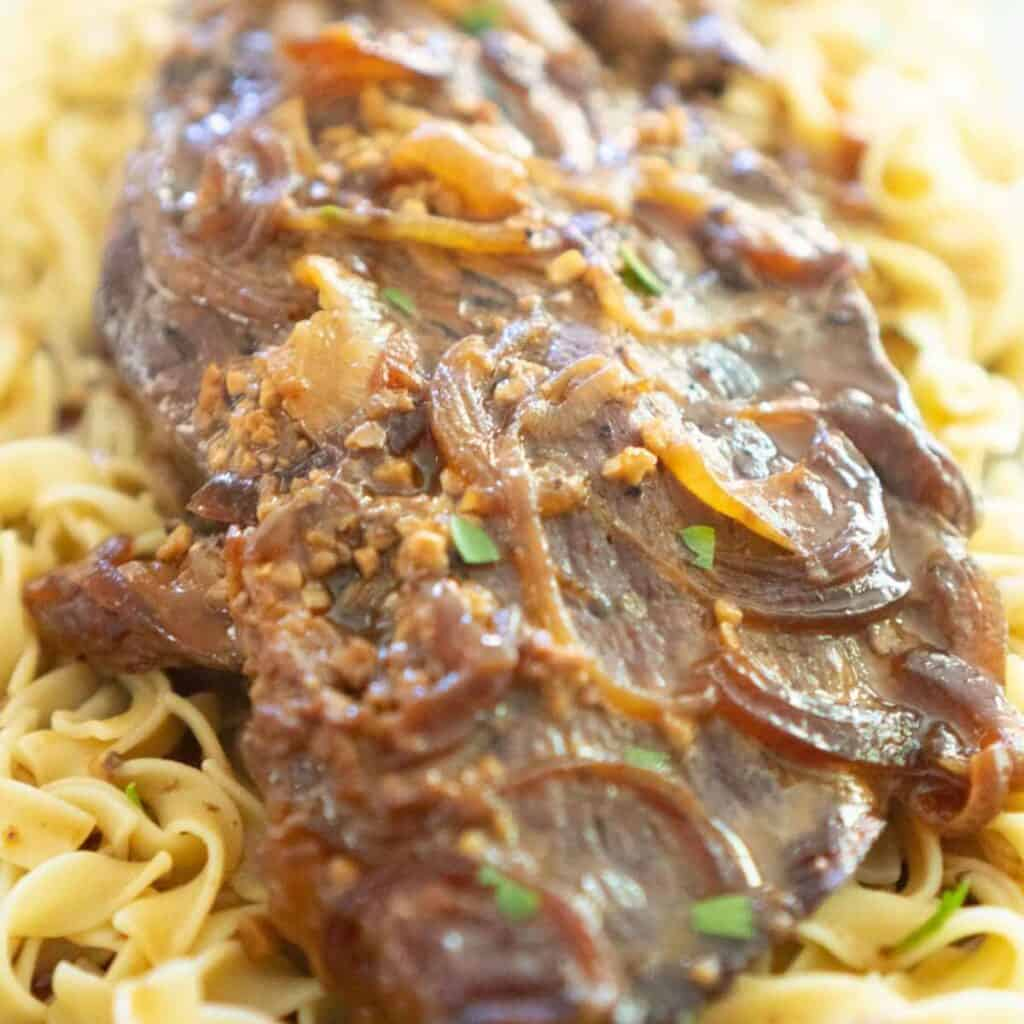 slow cooker london broil over egg noodles with onions and gravy