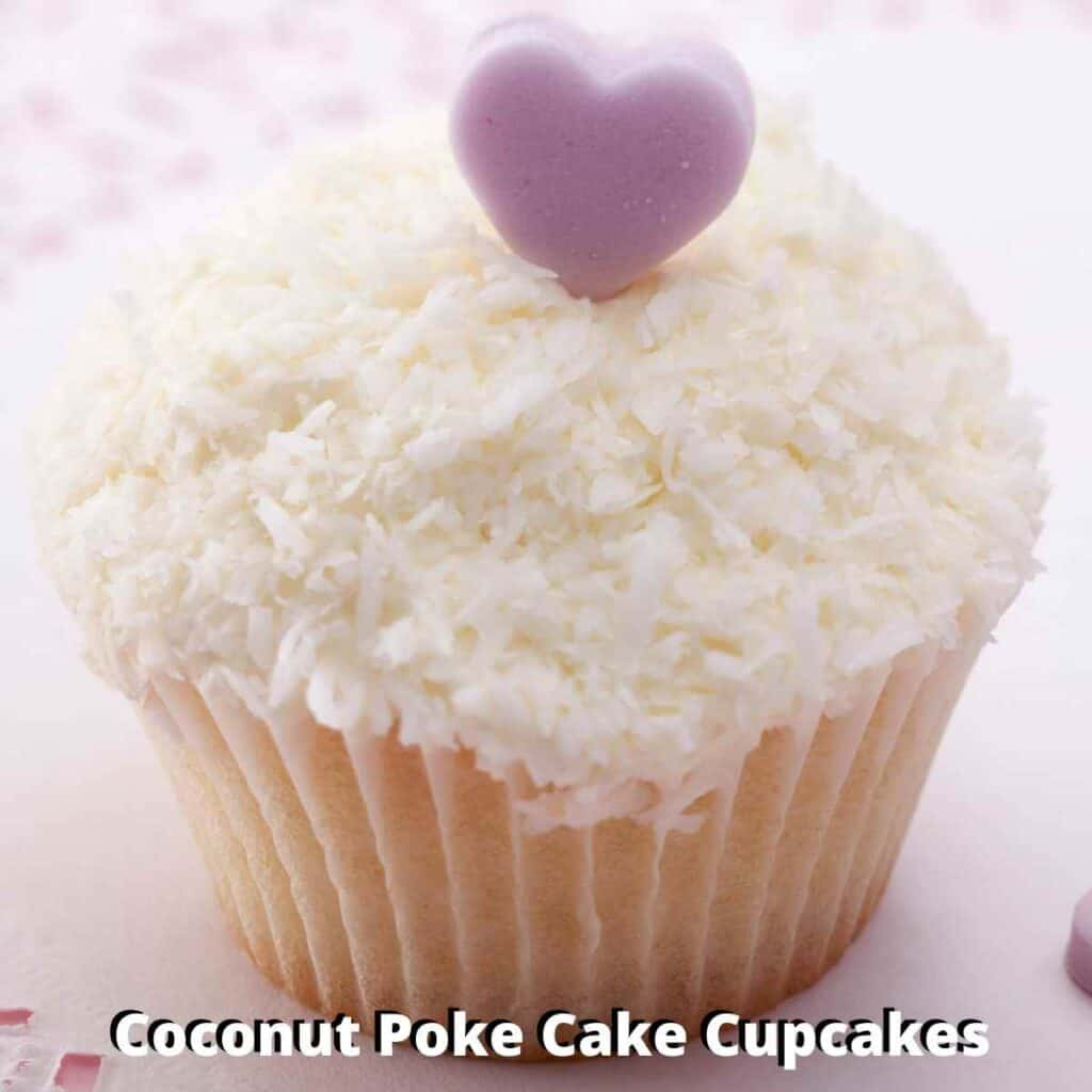 coconut creme poke cake cupcake topped with coconut frosting and shredded coconut with purple heart candy on top