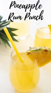 pineapple rum punch in stemless glass with slice of pineapple and yellow straw