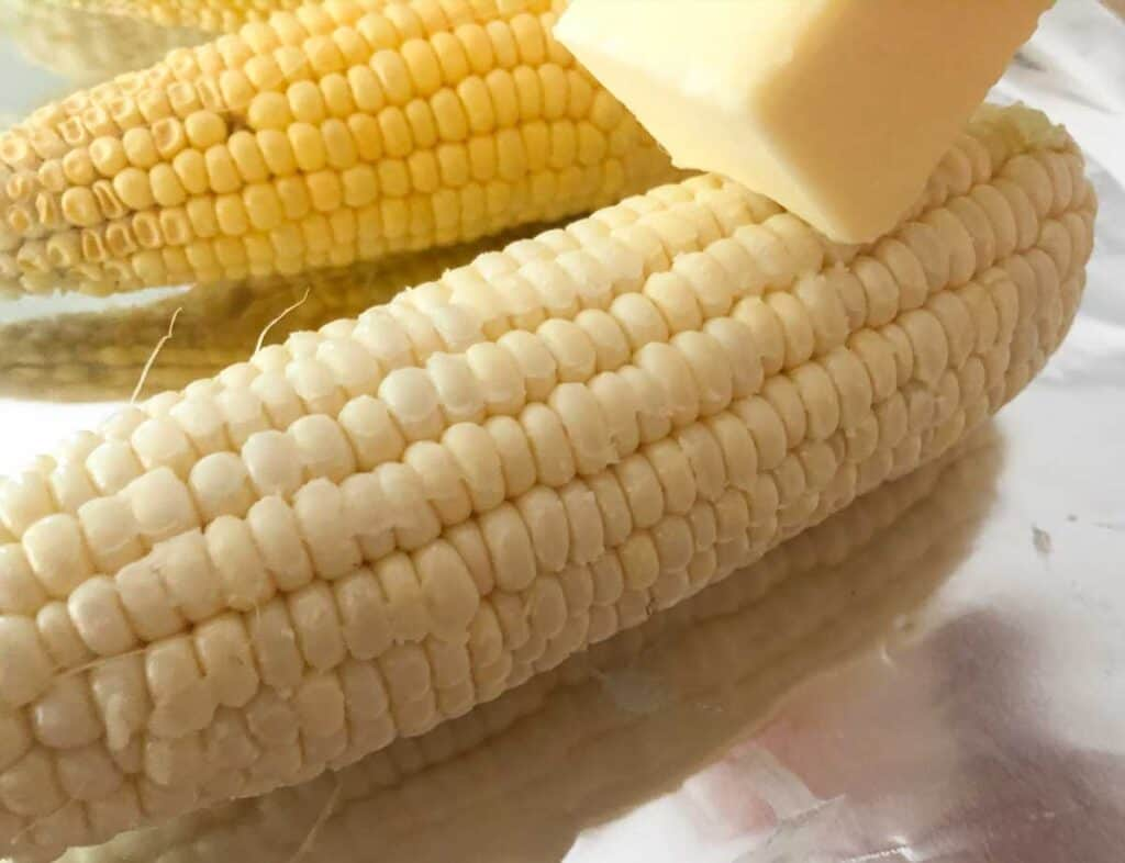 rubbing stick of butter over corn on the cob before grilling in foil